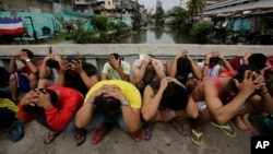 "FILE - Filipino men place their hands over their heads as they are rounded up during a police operation as part of the continuing ""War on Drugs"" campaign of Philippine President Rodrigo Duterte in Manila, Philippines."