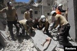 Arhiva - Pripadnici civilne zaštite tragaju za preživelima u ruševinama zgrade koja je uništena u vazdušnom udradu u pobunjeničkom gradu Ariha u pokrajini Idlib, Surija, 13. juli 2016.
