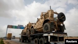 FILE - A trailer transports armored vehicles used by the North Atlantic Treaty Organization (NATO) forces during the Afghan war.