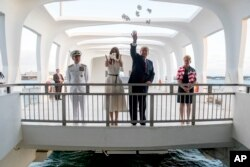 El presidente Trump y la primera dama Melania Trump, acompañados por el comandante de comando Harry Harris, y su esposa, Bruni Bradley, esparcieron pétalos de pikake mientras visitaban el Monumento de Pearl Harbor en Honolulu, Hawai, el 3 de noviembre de 2017.