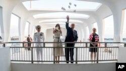 Rais Donald Trump na mkewe Melania Trump, wakiwa na Kamanda Admirali Harry Harris, kushoto, na mkewe Bruni Bradley, wakipeperusha maua walipotembelea eneo la kumbukumbu la Pearl Harbor Memorial katika mji wa Honolulu, Hawaii, Novemba. 3, 2017.