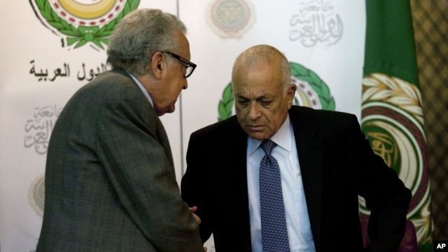 U.N.-Arab League envoy to Syria Lakhdar Brahimi, left, shakes hands with Arab League Secretary-General Nabil Elaraby following a joint press conference at the Arab League headquarters in Cairo, Egypt, December 30, 2012.