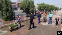 Iraqi municipality workers clean the scene of a suicide attack in Baghdad's western Eskan neighborhood, Iraq, Sunday, Sept. 25, 2016. A suicide bomber killed several people who were setting up tents on Sunday ahead of a major Shi'ite religious observance next month, officials said.