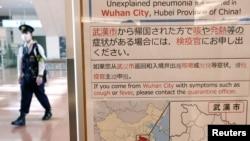日本东京羽田机场一名戴着口罩的警察走过武汉肺炎的防疫广告牌。(2020年1月20日)