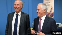 Conservative Liberal party MP John Alexander laughs as he stands with Australian Prime Minister Malcolm Turnbull during a visit to a printing company in Sydney, Australia, April 4, 2017.