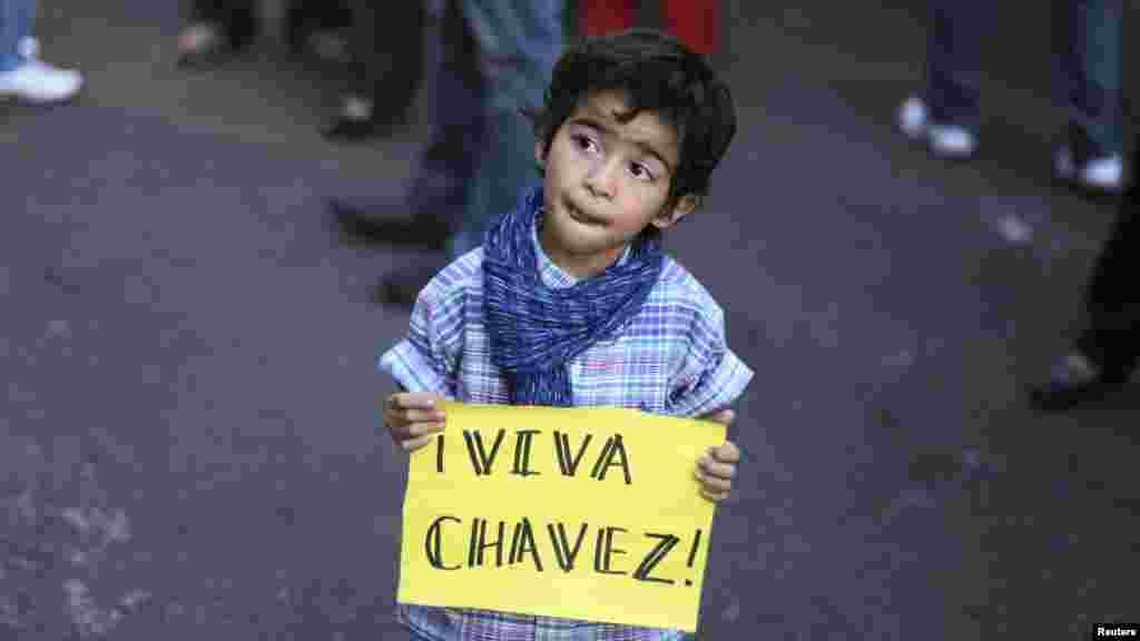 """2013年3月6日,一名小男孩在洪都拉斯首都特古西加尔巴手持""""查韦斯万岁""""的标语牌。"""
