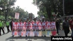 Aksi long march peringatan hari tani nasional di Jalan Medan Merdeka Selatan menuju Istana Merdeka, Jakarta, 27 September 2016. (Foto:VOA/Andylala).