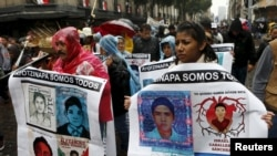 FILE - Relatives and friends hold banners with images of some of the 43 missing students of the Rural Normal School of Ayotzinapa as they march in Mexico City to mark the first anniversary of the students' disappearance, Sept. 26, 2015.