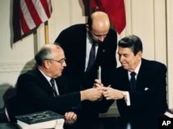 1987年苏联领导人戈尔巴乔夫和美国总统里根(右)在签署美苏中程核导弹条约后换笔(1987年12月8日)