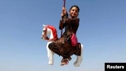 Una niña afgana en Kabul se divierte en un parque de atracciones en el primer día del festival sagrado musulmán de Eid-al-Adha.