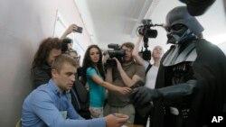 """در حاشیه نمایش فیلم قبلی جنگ ستارگان، شخصیت """"دارت ویدر"""" با طرفداران عکس می گیرد."""
