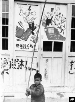 """历史照片:在上海,一名男孩拿着竹竿在""""绞死刘少奇""""的宣传画前嬉戏。(1967年5月27日)"""