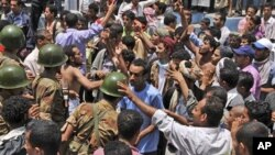 Yemeni army soldiers block the way as anti-government protestors attend a demonstration demanding the resignation of Yemeni President Ali Abdullah Saleh, in Taiz, Yemen, April 10, 2011