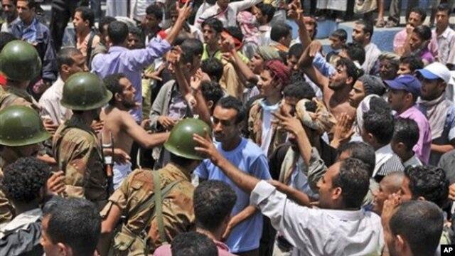Yemeni army soldiers block the way as anti-government protestors attend a demonstration demanding the resignation of Yemeni President Ali Abdullah Saleh, in Taiz, Yemen, April 10, 2011