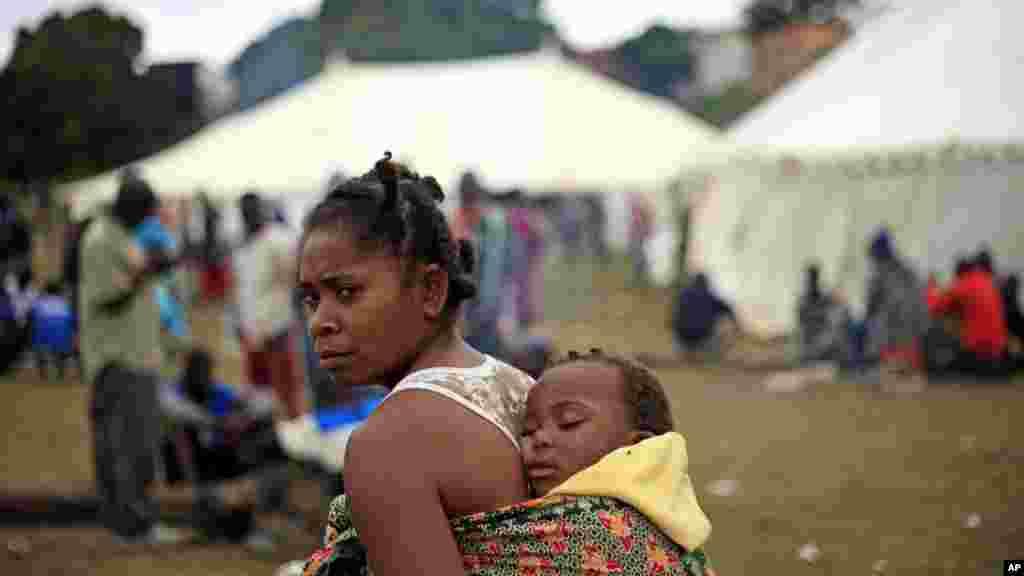 Un bébé sur le dos, une femme se promène dans un camp de réfugiés où plus de 2000 étrangers se sont abrités à Durban, en Afrique du Sud après les attaques meurtrières sur les immigrants, mercredi 15 avril 2015.