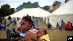 Une immigrante, son enfant sur le dos, vit dans un camp des réfugiés en Afrique du Sud, où elle fui la violence xénophobes des autochtones à Durban, mercredi 15 avril 2015