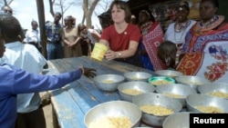 Catherine Bertini, former Executive Director of the World Food Programme (WFP), dishes out lunch to pupils, (File photo).