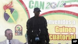"""A member of Equatorial Guinea's police special forces stands in front of a banner of President Teodoro Obiang Nguema Mbasogo outside Estadio de Bata """"Bata Stadium"""", which will host the opening match and ceremony for the African Nations Cup, in Bata Januar"""