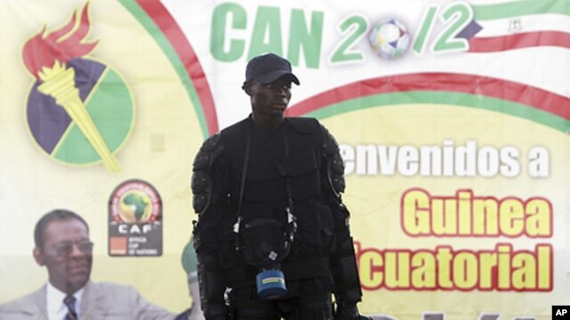 "A member of Equatorial Guinea's police special forces stands in front of a banner of President Teodoro Obiang Nguema Mbasogo outside Estadio de Bata ""Bata Stadium"", which will host the opening match and ceremony for the African Nations Cup, in Bata Januar"