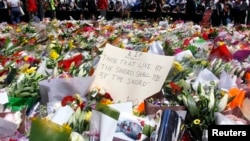 Members of the public stand behind a note that can be seen amongst floral tributes that have been placed near the cafe where hostages were held for over 16-hours, in central Sydney December 16, 2014. Heavily armed Australian police stormed a Sydney cafe e
