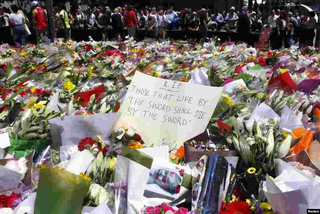 Members of the public stand behind floral tributes that have been placed near the cafe where hostages were held for over 16 hours, in central Sydney. Heavily armed Australian police stormed a Sydney cafe and freed a number of hostages being held there at gunpoint, in a dramatic end to a 16-hour siege in which three people including the attacker were killed.