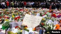 FILE - Members of the public stand behind a note that can be seen amongst floral tributes that have been placed near the cafe where hostages were held for over 16 hours, in central Sydney, Dec. 16, 2014.