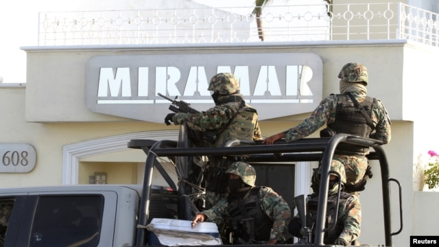 Military personnel stand atop a truck outside the Miramar building during a raid in Mazatlan, Feb. 22, 2014.