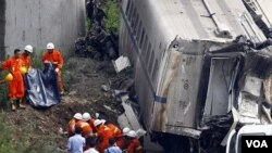 Regu penyelamat menggotong tubuh korban tewas yang ditemukan di antara rongsokan kereta api yang bertabrakan di Propinsi Zhejiang (24/7).