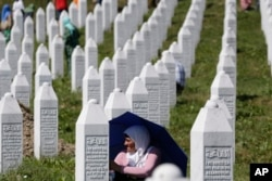 FILE - A Bosnian Muslim woman protects herself from the sun during a funeral ceremony for dozens of newly identified victims of the 1995 Srebrenica massacre, at the Potocari memorial center, near Srebrenica, 150 km northeast of Sarajevo, Bosnia, July 11, 2017.