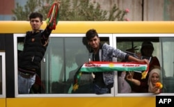 FILE - Iraqi Kurds wave fabric strips in the colors of the Kurdish flag during a rally in support of Iraqi Kurdish leader Masoud Barzani, in Irbil, Iraqi Kurdistan, Oct. 30, 2017.