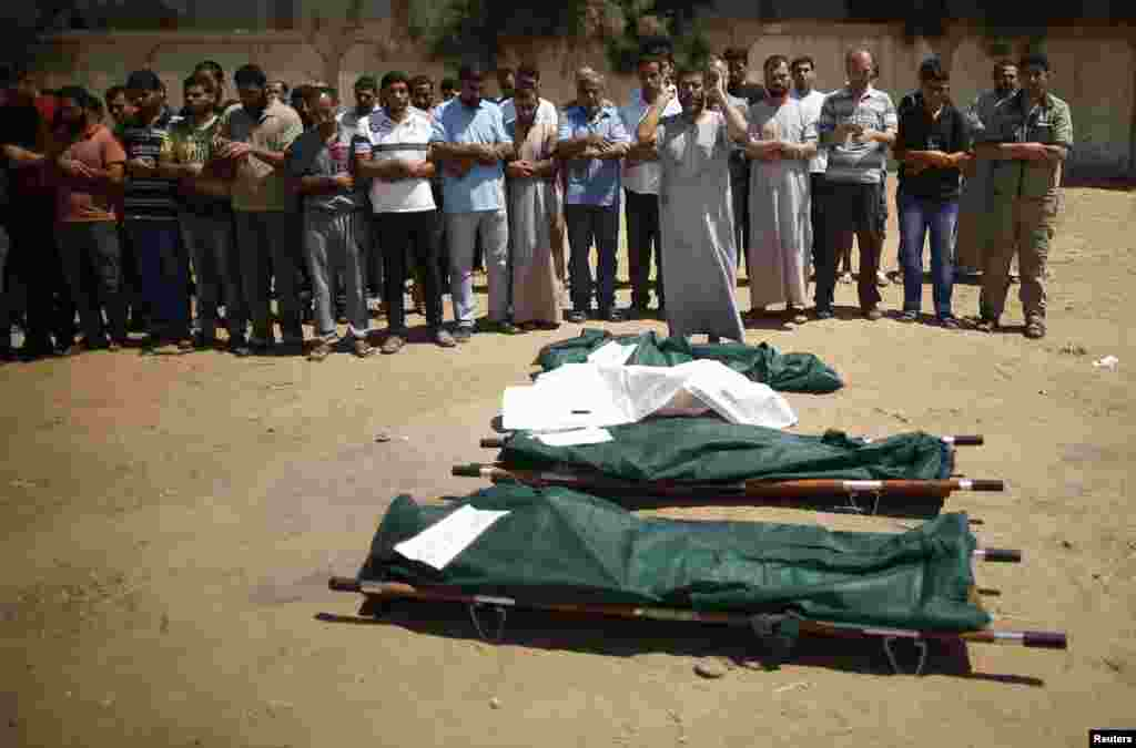 People pray next to the bodies of Palestinians from the al-Silk family during their funeral in Gaza City July 31, 2014.