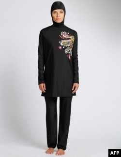 In a recent undated handout picture released by British retailer Marks and Spencer on April 8, 2016 a model poses wearing one of Marks and Spencer's full-body bathing suit or burkini suit.