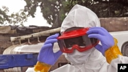 Petugas kesehatan Liberia memakai alat pelindung sebelum memindahkan jenazah pria yang diyakini mati karena Ebola di Monrovia (29/8). (AP/Abbas Dulleh)
