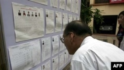Cử tri xem xét danh sách các ứng cử viên tại một địa điểm bỏ phiếu ở Hà Nội, ngày 22/5/2011