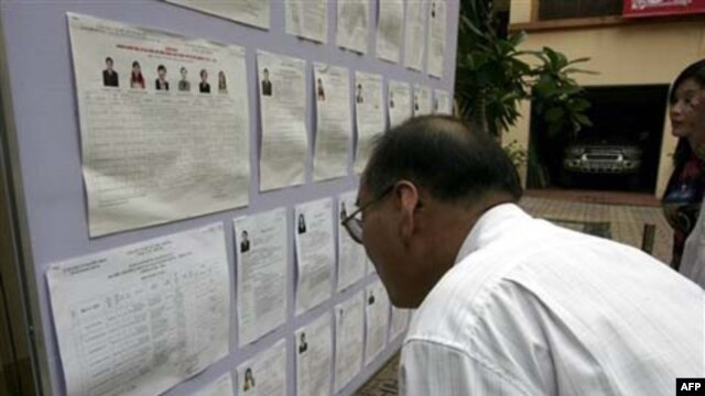 Một cử tri xem danh sách ứng cử viên ở Hà Nội