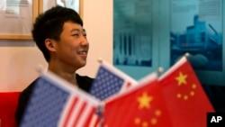 一位16岁的中国学生在北京一家教育机构里的美中两国国旗旁(2014年6月26日)