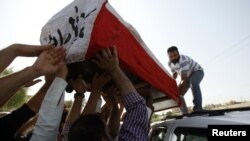Residents transport the coffin of the former governor of Basra Mohammed Musabih Al-Waili during his funeral in Basra, September 28, 2012.