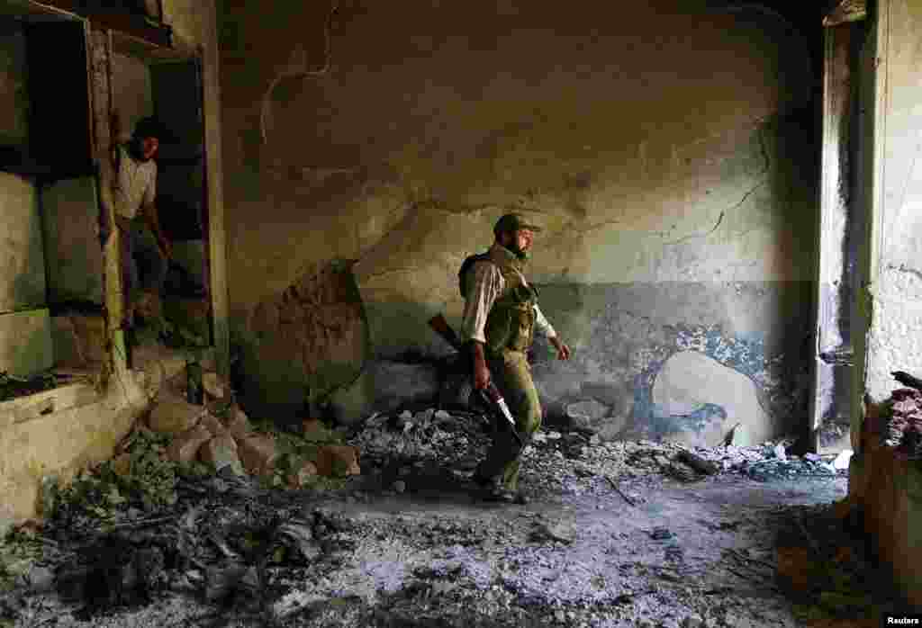 Free Syrian Army fighters walk inside a damaged house near the Hanano Barracks in Aleppo, Sept. 3, 2013.