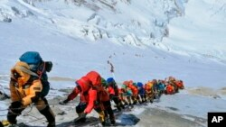 In this May 22, 2019 photo, a long queue of mountain climbers line a path on Mount Everest just below camp four, in Nepal. (AP Photo/Rizza Alee)
