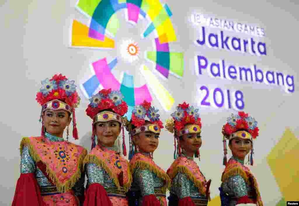 عکسی از دختران اندونزیایی با لباسهای سنتی مقابل لوگو هجدهمین دوره بازی های آسیایی به میزبانی جاکارتا.