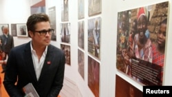 FILE - Actor Brad Pitt looks at photographs at a fringe event of a summit to end sexual violence in conflict in London.