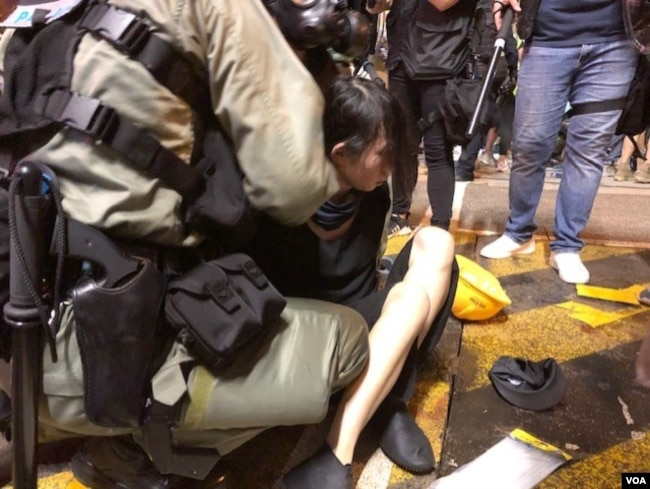 香港防暴警察在上环清场中拘捕一位女孩 (美国之音海彦拍摄 )