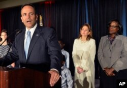 With his wife Glenna Bevin, center, and Lieutenant Governor-elect Jenean Hampton, right, looking on, Kentucky Republican Governor-elect Matt Bevin, speaks to his supporters at the Republican Party victory celebration, Tuesday, Nov. 3, 2015, in Louisville,
