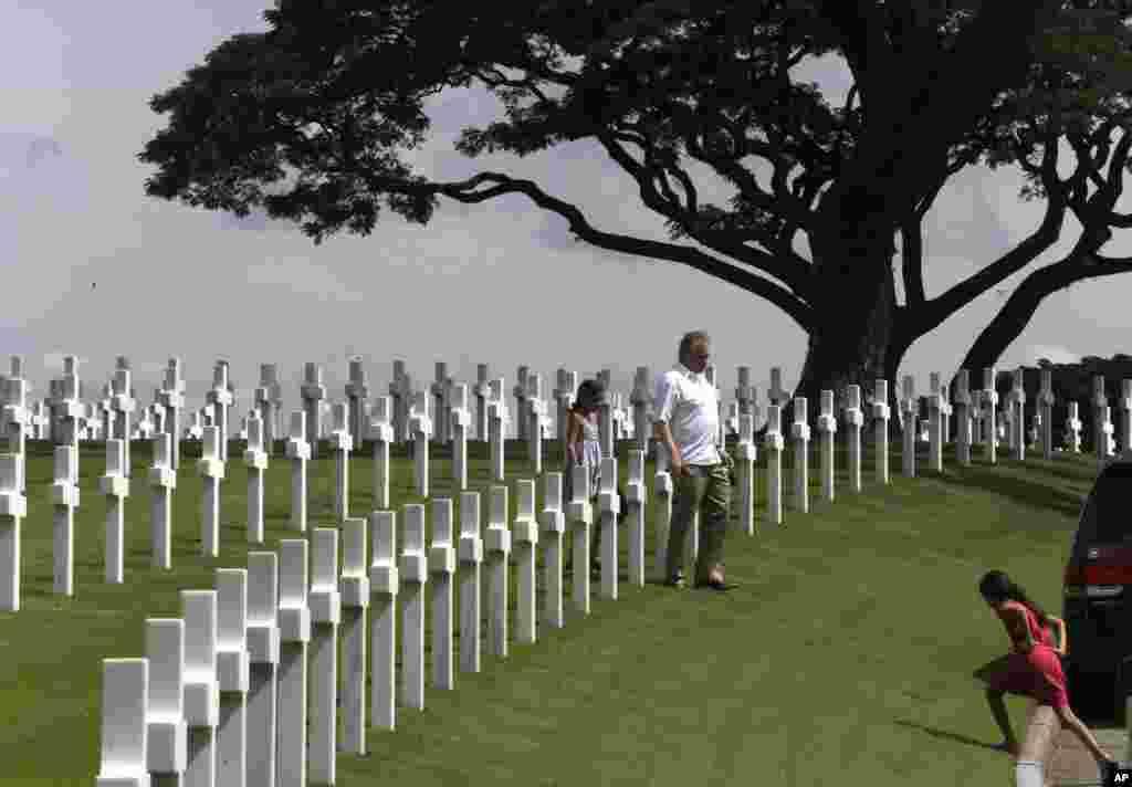 Công dân Mỹ ở Philippines len qua những hàng thập tự giá sau buổi lễ đặt vòng hoa kỷ niệm Ngày Cựu chiến binh của Mỹ tại Nghĩa trang Mỹ ở thành phố ngoại ô Taguig, phía đông thủ đô Manila, ngày 11 tháng 11, 2012. (AP)
