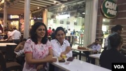 Sonal Jain (right in white shirt) takes a break from office to relax over a cup of tea with a friend. (A. Pasricha/VOA)
