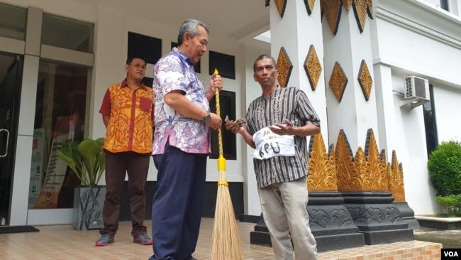 Sapu dan uang mainan diserahkan ke KPU DIY sebagai sindiran atas dugaan kasus suap di KPU RI. (foto VOA/Nurhadi)