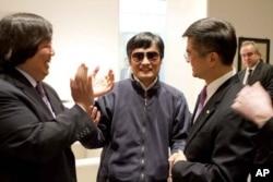 នៅក្នុងរូបថតដែលចេញផ្សាយដោយការិយាល័យព័ត៌មានស្ថានទូតអាមេរិកនៅក្រុងប៉េកាំង អ្នកច្បាប់ពិការភ្នែកលោក Chen Guangcheng (កណ្តាល) ចាប់ដៃជាមួយឯកអគ្គរដ្ឋទូតអាមេរិកប្រចាំនៅប្រទេសចិន លោក Gary Locke (ស្តាំ)។