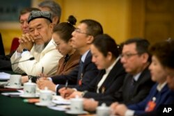 A delegate in traditional Uighur dress listens to a speaker during a group discussion meeting with delegates from China's Xinjiang Uighur Autonomous Region on the sidelines of China's National People's Congress (NPC) at the Great Hall of the People in Beijing, March 12, 2019.