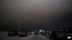 Traffic makes their way south on I-15 as ash from the Holy Fire fills the air on Aug. 9, 2018 in Lake Elsinore, Calif.