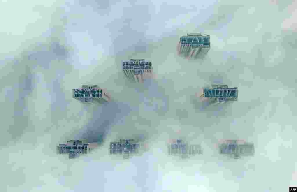 This aerial view shows the tops of high-rise buildings poking out from heavy fog in Yangzhou, in China's eastern Jiangsu province.